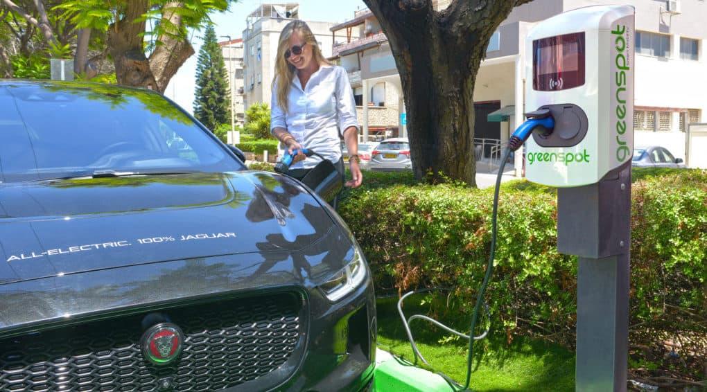 אישה מחברת רכב מסוג יגואר לעמדת טעינה ציבורית של גרינספוט