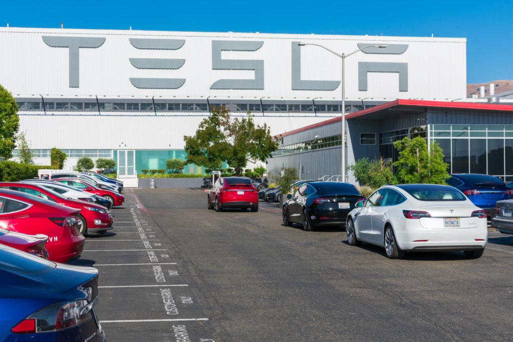 חוץ המפעל של טסלה בפרימונט קליפורניה עם הלוגו של טסלה בגדול