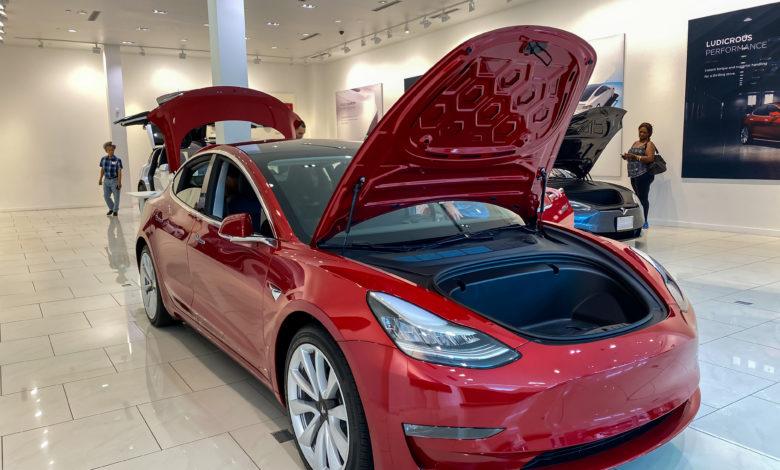 טסלה מודל 3 בצבע אדום באולם תצוגה של טסלה עם תא המטען הקדמי ותא המטען האחורי פתוחים