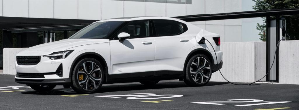 פולסטאר 2 חשמלית בצבע לבן עומדת בחניה ומחוברת לעמדת טעינה לרכב חשמלי