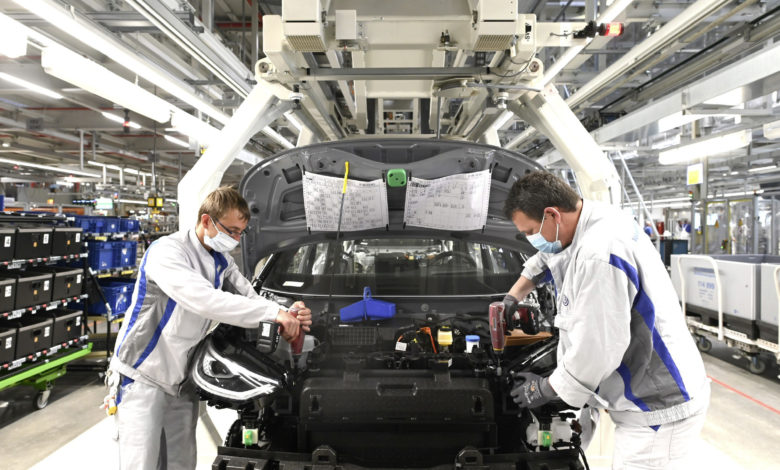 שני עובדים במפעל של פולקסווגן בגרמניה בתהליך ההרכבה של ה-ID.3 החשמלית