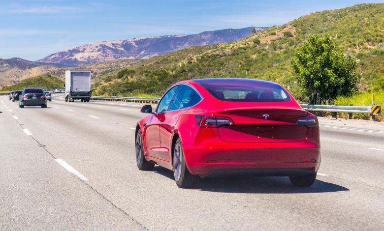 טסלה מודל 3 אדומה על כביש מהיר בקליפורניה