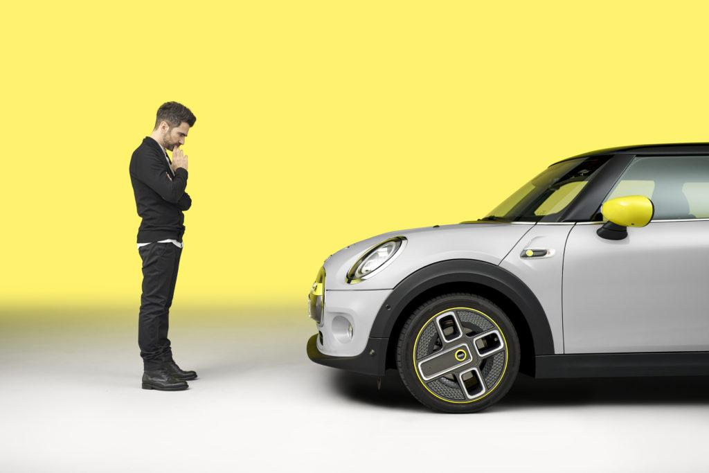 אדם בוהה ברכב מיני קופר חשמלית בצבע לבן עם אלמנטים צהובים ורקע צהוב לבן
