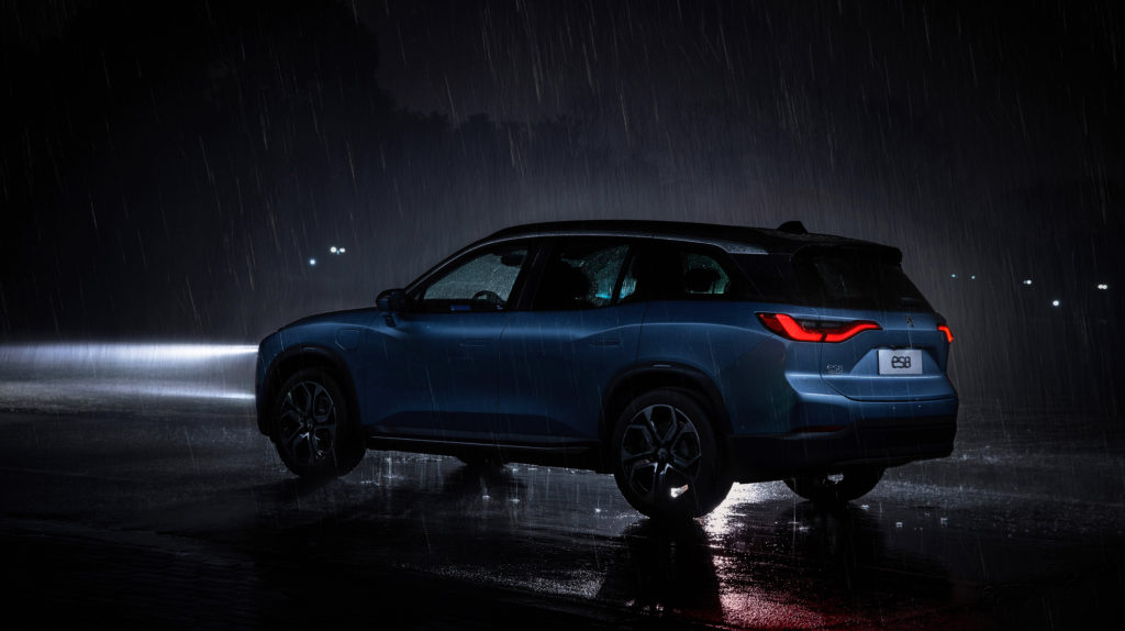 ניו ES8 בצבע כחול במבט מהצד בגשם בחושך עם אורות קדמיים דלוקים