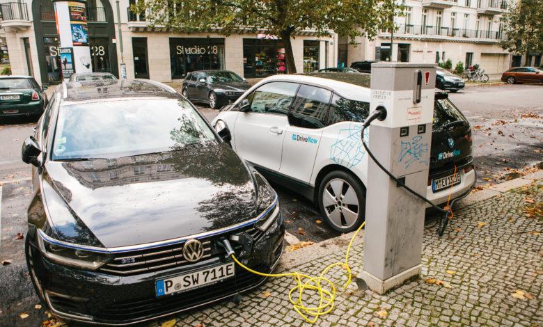 שני רכבים חשמליים, גולף חשמלית וב.מ.וו i3 מחוברים לעמדת טעינה ברחוב בברלין גרמניה