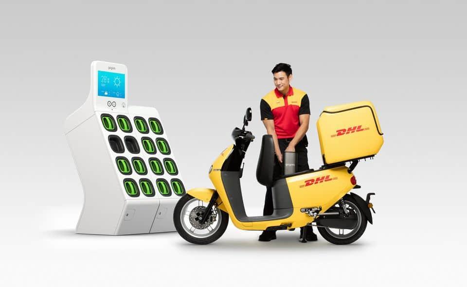 שליח של DHL עם קטנוע משלוחים חשמלי של גוגורו עם כוורת הטענה לסוללות