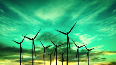 טורבינות רוח לייצור אנרגיה ברקע שמיים מעוננים ירוקים