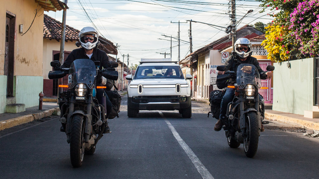 שני אופנועים חשמליים עם רכב חשמלי של ריביאן מאחוריהם