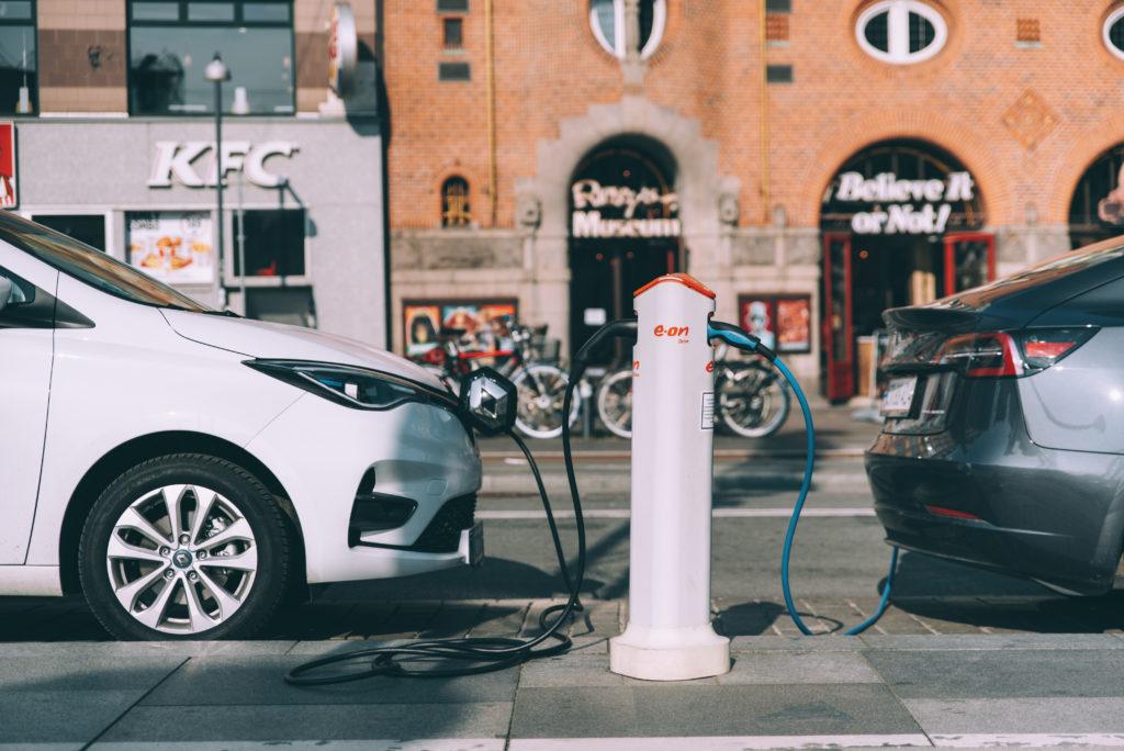 רנו זואי וטסלה חונות ברחוב ומחוברות לעמדת טעינה לרכב חשמלי בקופנהגן דנמרק