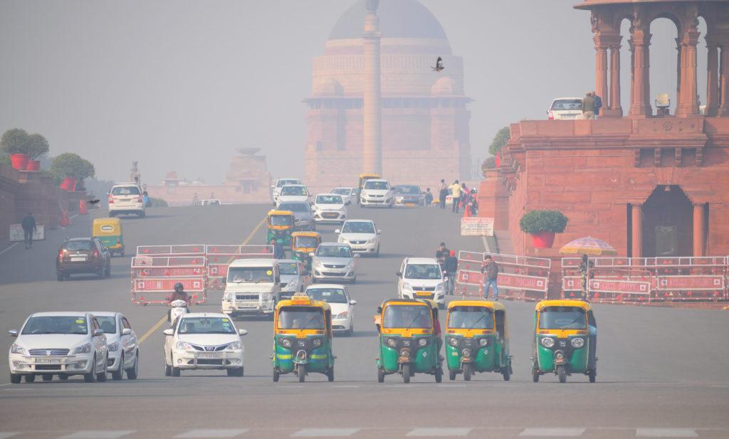מספר ריקשות ורכבים על כביש בדלהי עם זיהום אוויר שגורם לערפל