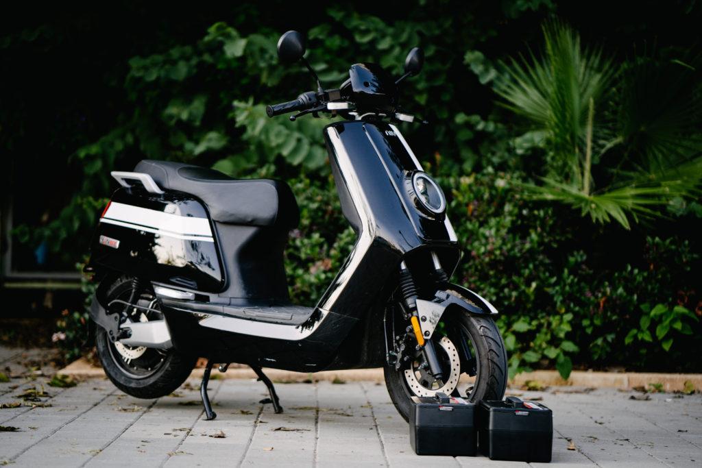 קטנוע חשמלי של NIU עומד על המדרכה עם שתי סוללות לידו