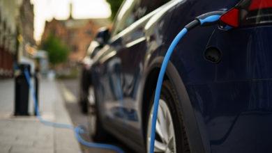 רכב חשמלי של טסלה בצבע שחור מחובר לעמדת טעינה בחניה רחוב