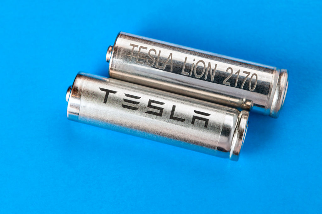 שתי סוללות ליתיום-יון עם לוגו של טסלה עליהן על רקע כחול בהיר