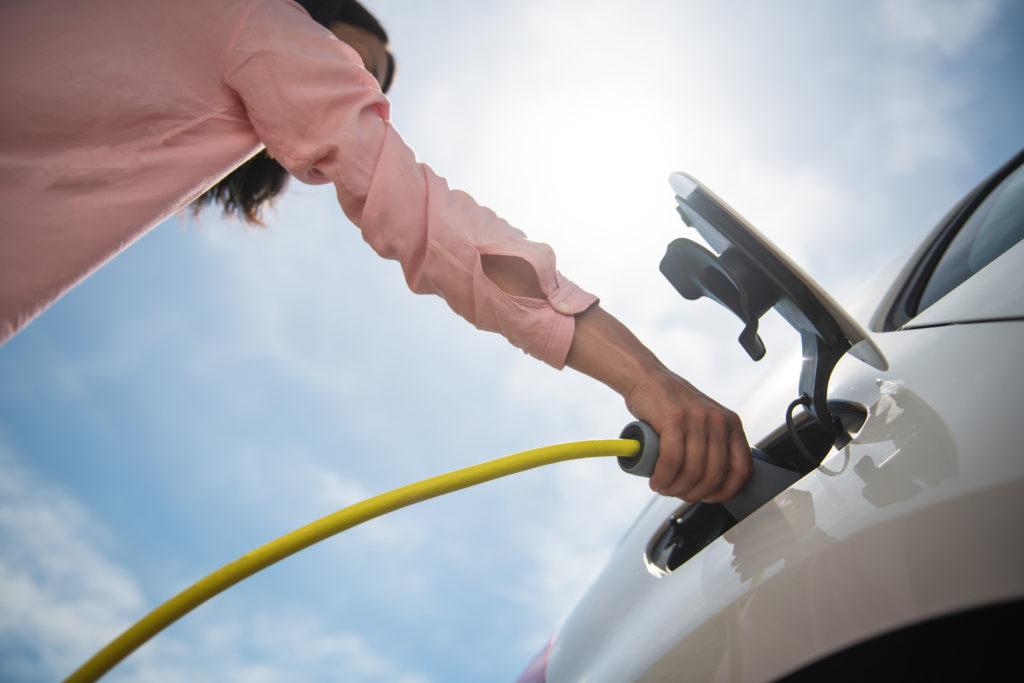 אישה מחברת רכב חשמלי לעמדת טעינה, צילום מלמטה