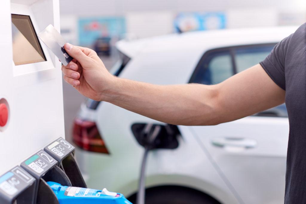 גבר משלם עם כרטיס אשראי בעמדת טעינה מהירה לרכב חשמלי כשמאחוריו רכב חשמלי לבן מחובר לעמדת טעינה