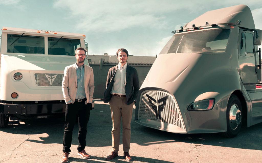 המייסדים של חברת Xos Trucks ליד שתי משאיות חשמליות של החברה