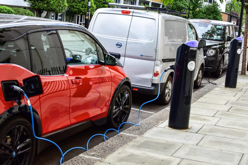 ב.מ.וו i3, מיניוואן חשמלי של ניסאן ומונית שחורה חשמלית מחוברת לעמדות טעינה לרכב חשמלי ברחובות לונדון בריטניה