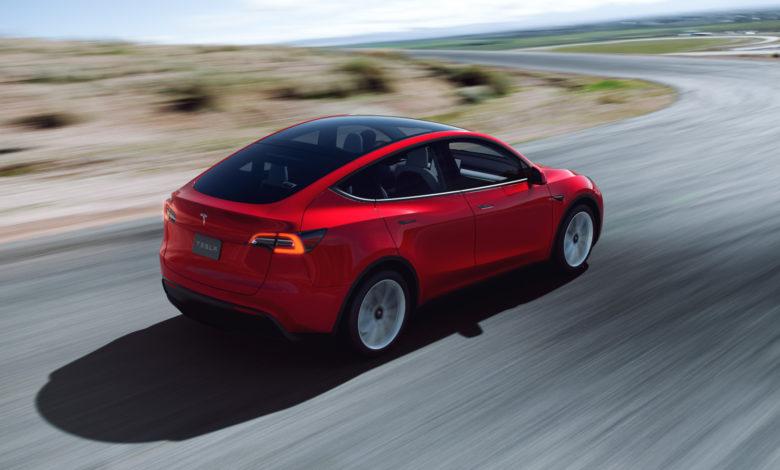 טסלה מודל Y בצבע אדום בנסיעה על כביש, מבט מאחורי הרכב