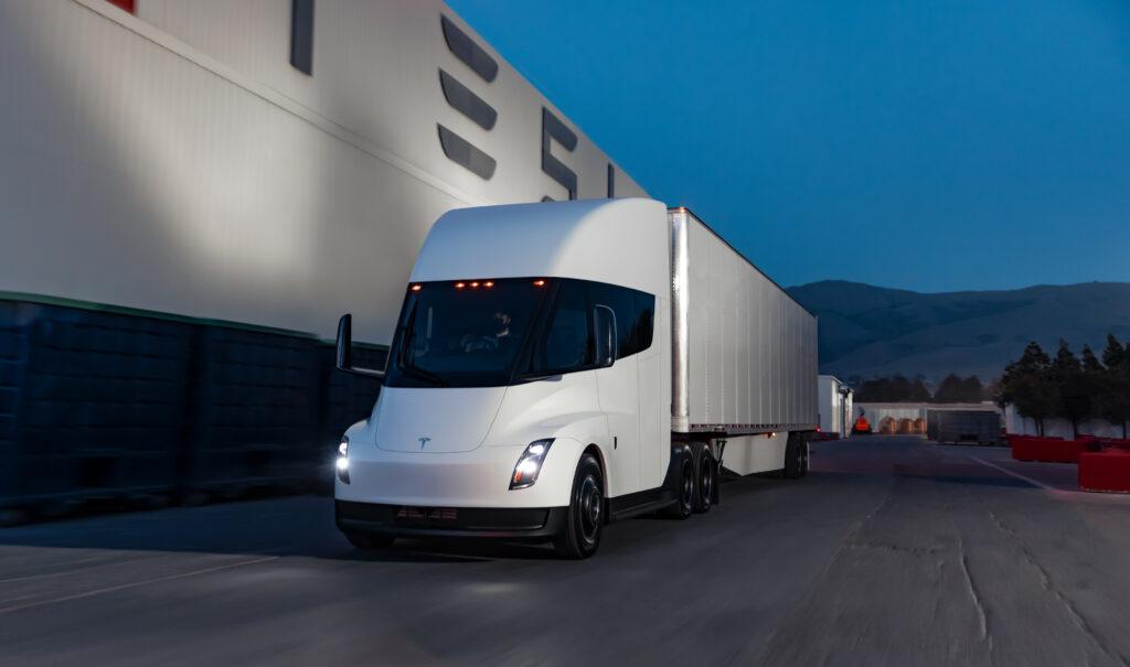 משאית טסלה סמי חשמלית בצבע לבן ליד מפעל של טסלה