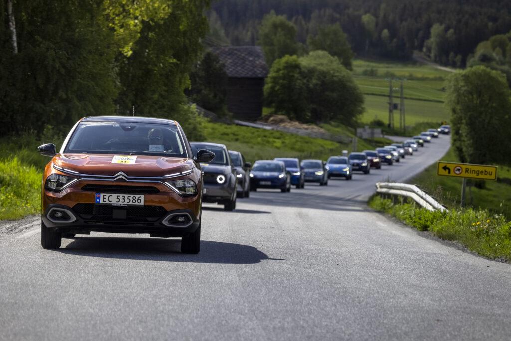 שיירה של רכבים חשמליים נוסעים על כביש בנורווגיה בזמן בחינת טווח הנסיעה שלהם