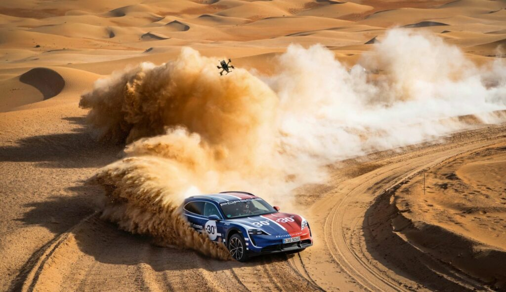 פורשה טייקאן במדבר בשטח עם רחפן מעליה שמצלם אותה