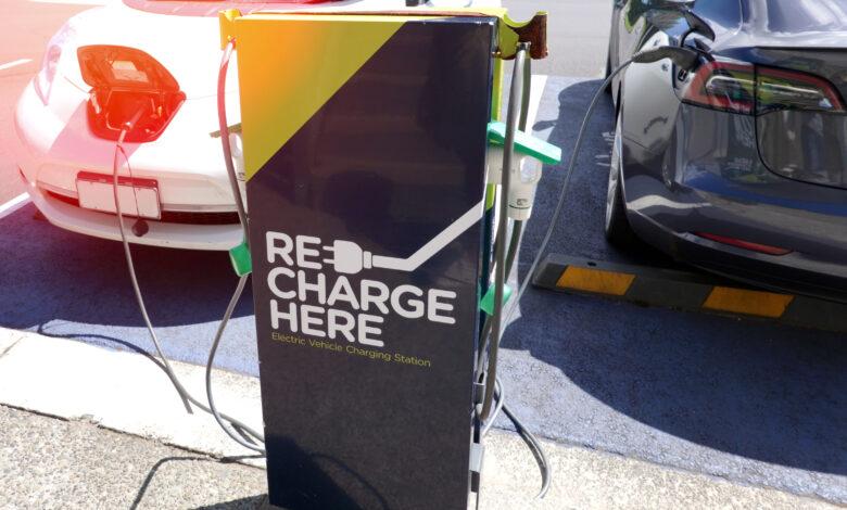 טסלה מודל S וניסאן ליף מחוברת לעמדת טעינה בניו זילנד עם הכיתוב Re Charge Here
