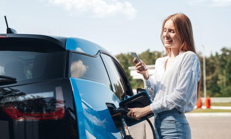 אישה מחברת את הרכב החשמלי שלה לעמדת טעינה