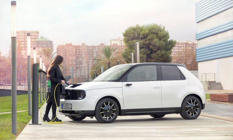 אישה מחברת את הונדה e החשמלית לעמדת טעינה לרכב חשמלי