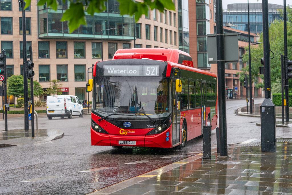 אוטובוס חשמלי מלא של חברת BYD בצבע אדום נוסע ברחובות לונדון בחורף