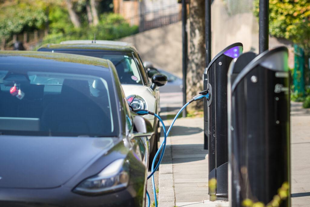 עמדות טעינה פרוסות לאורך הרחוב עם רכבים חשמליים מחוברים אליהן בלונדון