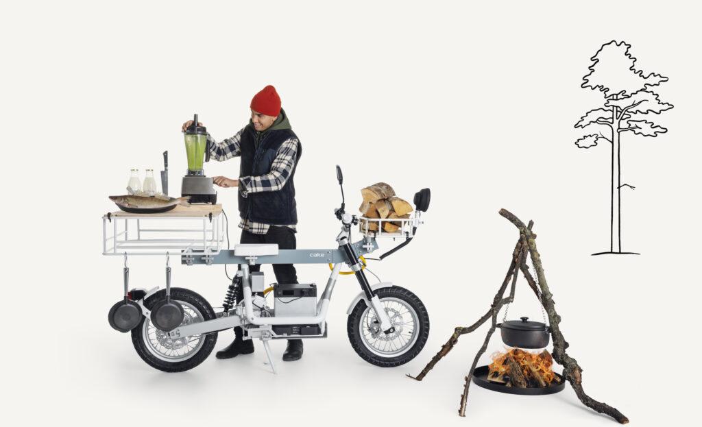 אדם מבשל על האופנוע החשמלי של קייק