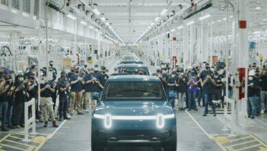 הרכבים הראשונים של ריביאן יוצאים מהמפעל עם העובדים מסביב הרכבים בהתרגשות