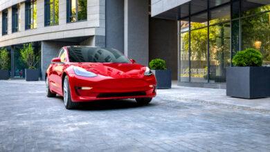 טסלה מודל 3 אדומה בנסיעה באיזור עירוני