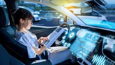 אישה יושבת במושר הנהג של רכב אוטונומי מתקדם וקוראת מגזין בזמן שהרכב נמצא במצב נהיגה