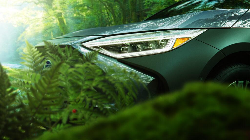 הפנס הקדמי של סובארו סולטרה EV החשמלית החדשה מגיח בין צמחיה בשטח