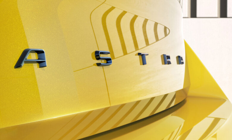 הכיתוב ASTRA מאחורי הדמיה של רכב אופל אסטרה חשמלית בצבע צהוב